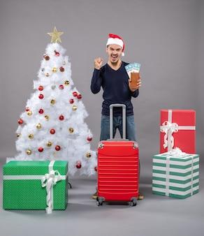 Gioì giovane con la valigia rossa che mostra i suoi biglietti di viaggio su grigio