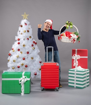 Rejoiced young man with santa hat holding gift basket near xmas tree on grey