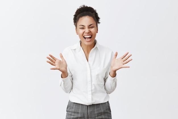 幸せに笑って手をたたくアフリカ系アメリカ人の女性を喜んで、実業家は目標を達成します