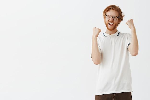Радующийся и торжествующий бородатый рыжий парень позирует на фоне белой стены в очках