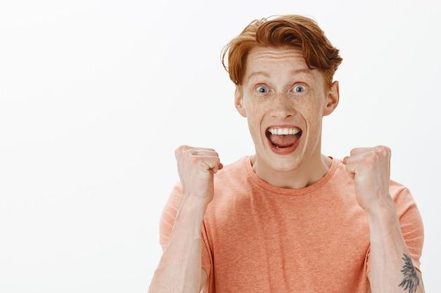Радостный привлекательный рыжий мужчина выглядит оптимистично, празднует фантастические новости, торжествуя над белой стеной