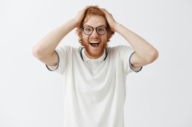Ragazzo di redhead barbuto gioire in posa contro il muro bianco con gli occhiali