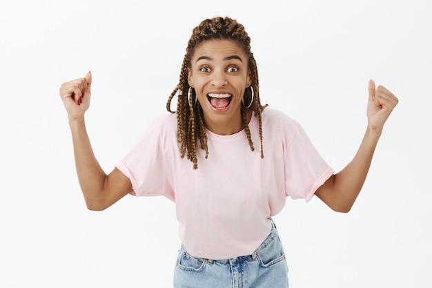 Радостная счастливая афро-американская женщина танцует и улыбается счастливой, торжествуя