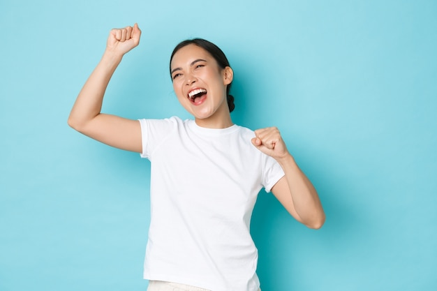 Rejoicing happy asian woman celebrating victory. euphoric girl triumphing over achievement, fist pump and shouting yes delighted, standing encouraged and confident, blue background.