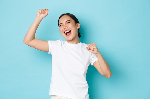 勝利を祝う幸せなアジアの女性を喜ぶ。達成に打ち勝つ陶酔感のある女の子、拳ポンプと叫び声は喜んで、励まされて自信を持って立っている、青い背景。