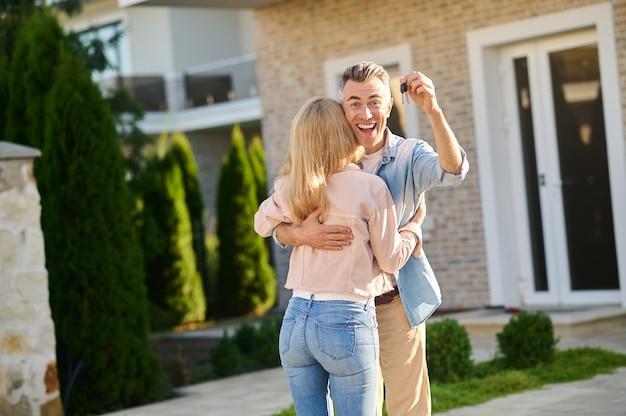 그의 아내를 포옹 하는 열쇠와 함께 기뻐하는 남자