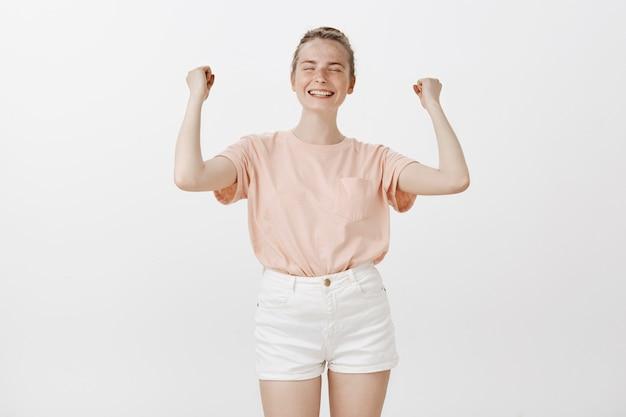 Радуясь девочка-подросток позирует у белой стены