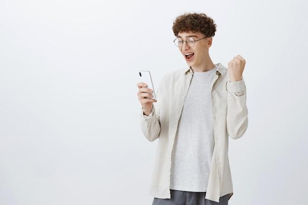 Радующийся парень-подросток позирует у белой стены