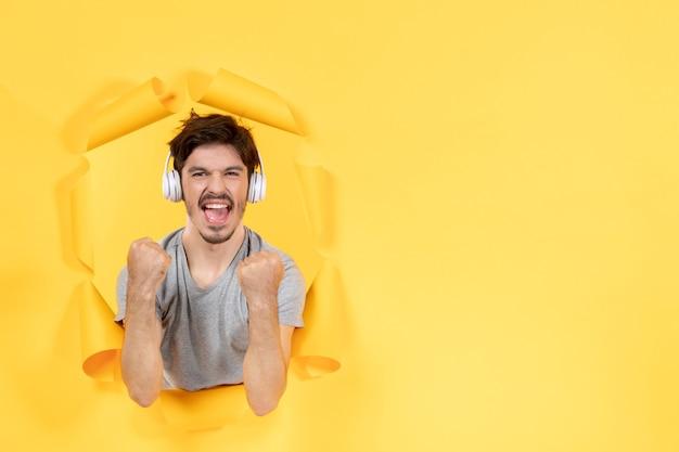 찢어진 노란 종이 배경 초음파 오디오 사운드에 헤드폰을 끼고 기뻐하는 젊은 남성
