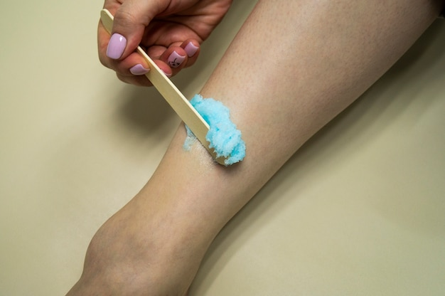 Rejuvenation procedure. the girl puts a blue scrub on her leg