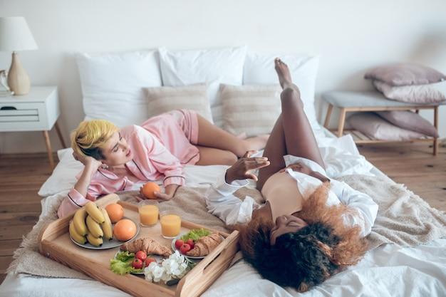 関係。自宅で朝の朝食をとっているベッドに横たわって寝ている服を着た2人の若い女性