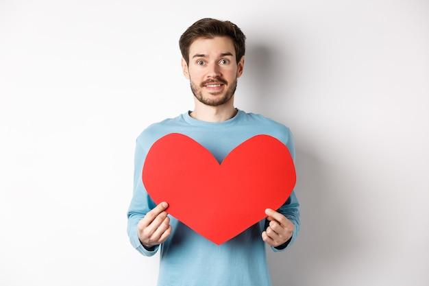 関係と愛の概念。大きな赤いバレンタインデーのハートのカットアウトを保持し、笑顔で、日付を告白し、白い背景の上に立って、セーターを着たハンサムな白人男性。