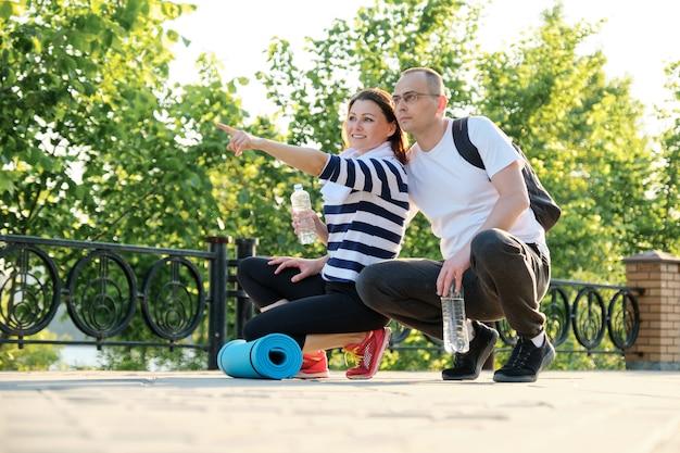 Отношения между людьми среднего возраста, пара разговаривает, отдыхает после фитнеса в парке