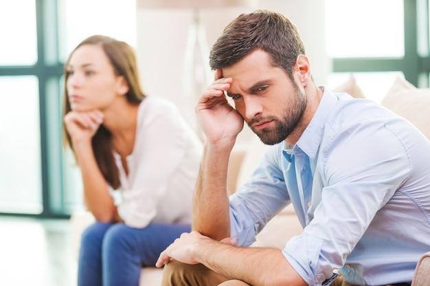 Распад отношений. подавленный молодой человек держит руку на голове и смотрит в сторону, пока женщина сидит за ним на диване