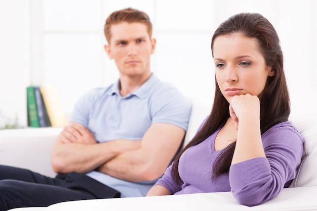 관계 붕괴. 우울한 젊은 여성이 턱에 손을 대고 시선을 돌리고 남자는 소파에 그녀 뒤에 앉아 팔짱을 끼고 있다