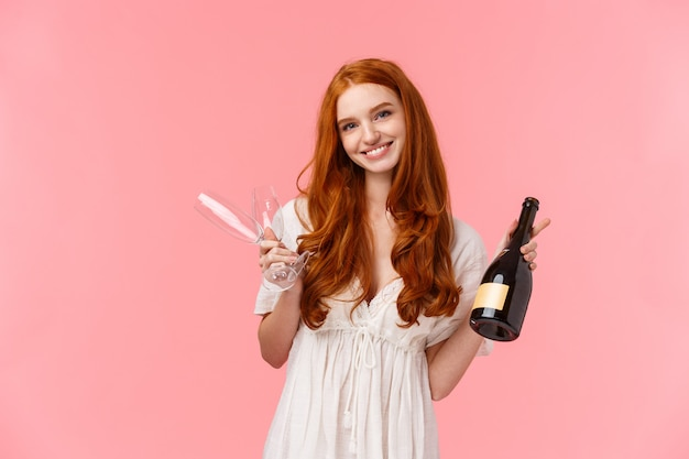 Relationship, celebration and tenderness concept. lovely caucasian girl with red long curly hair in white dress, inviting have drink together, holding champagne and two glasses, smiling