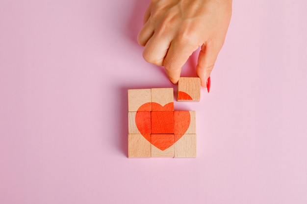 Relationship concept flat lay. finger pulling out wooden block.