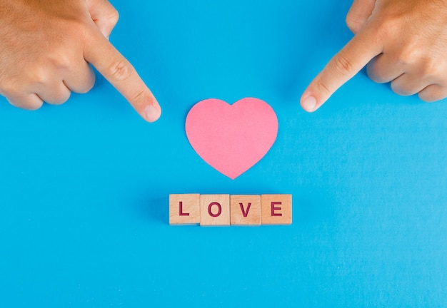 Relationship concept with wooden cubes on blue table flat lay. fingers showing paper cut heart.