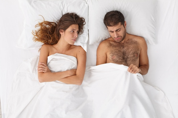 Relationship difficulties, impotence concept. stressed married couple have marital problems because of mans erectile dysfunction, problems with man health, pose in bedroom. intimacy troubles.
