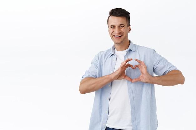 Концепция отношений, эмоций и чувств. портрет счастливого прекрасного парня, показывающего знак сердца над грудью, широко улыбающегося, например, показывающего привязанность или сочувствие, стоящего у белой стены