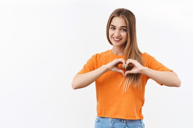 人間関係、感情、若者のコンセプト。オレンジ色のtシャツを着た明るく魅力的なブロンドの女の子の肖像画、愛、ケア、共感を表現するために胸にハートのサインを表示し、何かに情熱を注ぐ