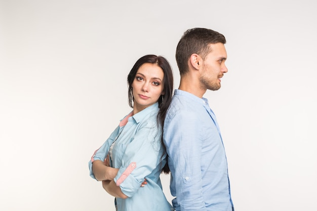 Отношения, семейный конфликт и люди концепции. молодая пара стоит спиной к спине на белом