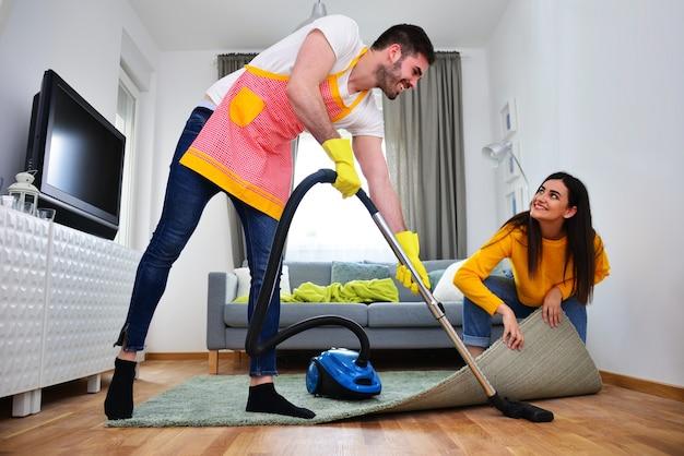 관계, 결혼 생활, 가사 노동 및 의무, 남녀 평등 개념. 여자가 그를 돕는 동안 청소하는 남자.