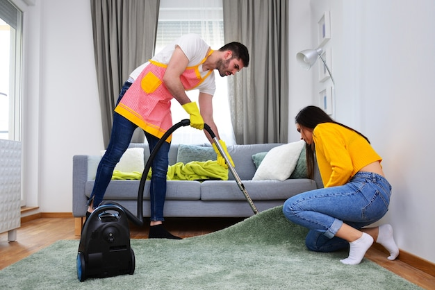 Relationship, married life, household works and duties, gender equality concept. man cleaning while woman is assisting him,.
