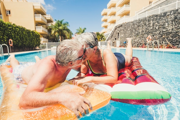Relationship for mature retired people adult couple kissing in the swimming pool having fun with trendy lilos together in a sunny day of summer holiday vacation in the hotel