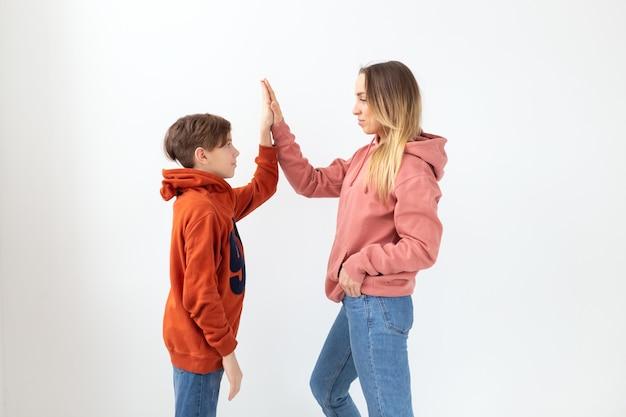 Отношения, день матери, дети и концепция семьи - мать и сын, одетые в толстовки, высокие пять жестов.