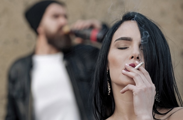 Relationship of sensul couple sexy man and woman girl smoking cigarette with smoke and blurred brutal man drinking wine