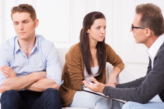 Проблемы в отношениях. недовольная молодая пара сидит на диване и смотрит в сторону, пока психиатр разговаривает с ними и жестикулирует