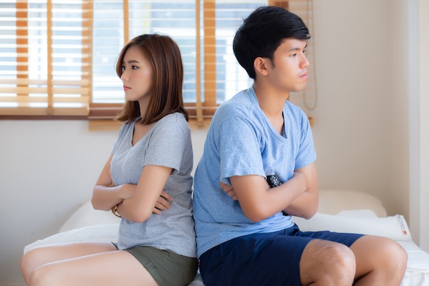 Relationship of young asian couple having problem on bed in the bedroom