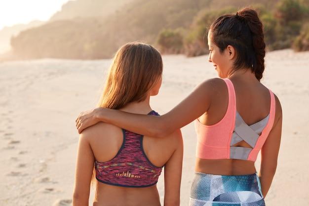 Concetto di relazioni. vista posteriore della madre affettuosa abbraccia la figlia adolescente
