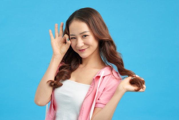 Relax all good. carefree and chill cute asian girl winking camera saying alright,  show okay gesture, approve or agree with person