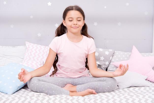 リラックスして、睡眠への移行を容易にします。就寝時のコンセプト。就寝前にリラックスする方法。眠りにつくためのリラクゼーションエクササイズ。パジャマ姿の少女が就寝の準備をします。子供のための心を落ち着かせる活動。