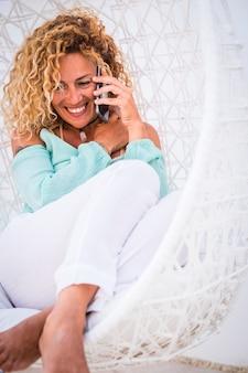 Расслабьтесь и наслаждайтесь концепцией роскошных людей - довольно блондинка взрослая жизнерадостная женщина сидит на гамаке или белом большом деревянном яйце - дама с длинными вьющимися волосами звонит и разговаривает по телефону дома