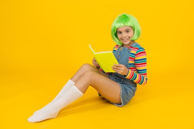 Расслабьтесь и читайте книгу. прелестный маленький ребенок читал книгу желтом фоне. милая маленькая девочка любит читать. счастье не купишь, но книгу можно купить. книжный магазин. библиотека. bibliopole.