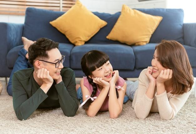 행복과 함께 누워 아시아 가족을 휴식을 취하고 집에서 거실 카펫에 미소. 평면도