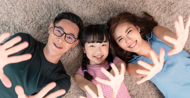 집 거실에 있는 카펫에 행복하고 미소를 지으며 누워 있는 아시아 가족을 편안하게 하세요. 평면도