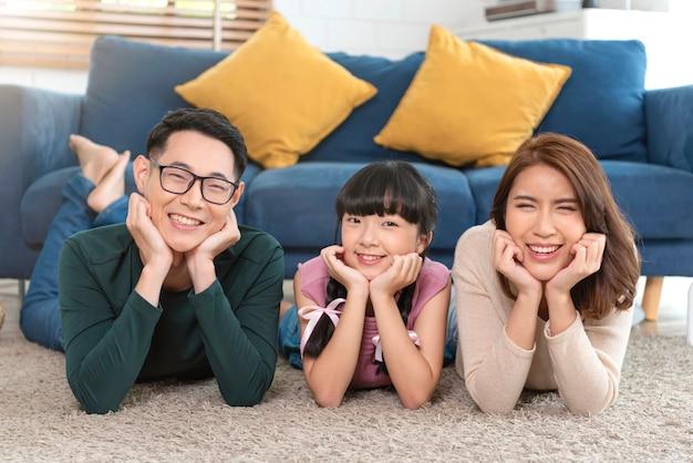 自宅のリビングルームのカーペットの上に幸せと笑顔で横たわっているアジアの家族をリラックスしてください。