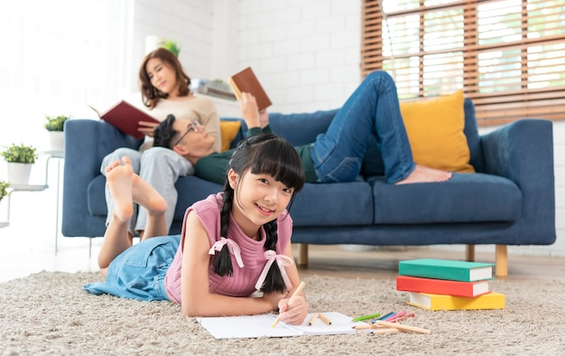 Relax asian parent reading a book on sofa and daughter painting art in living room at home
