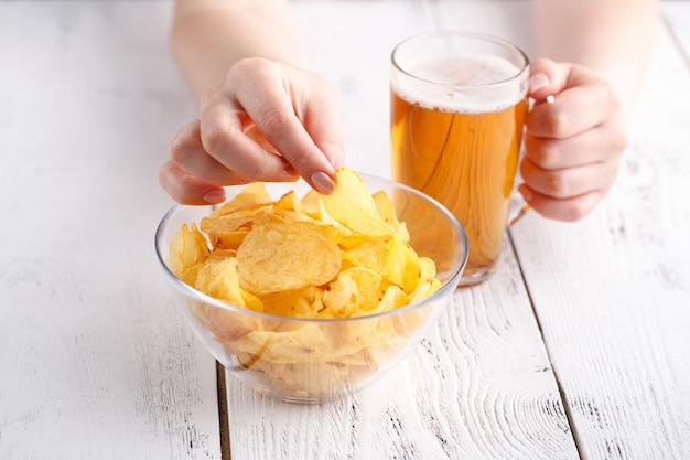 自宅で女性のビールとポテトチップスでディナーをリラックス