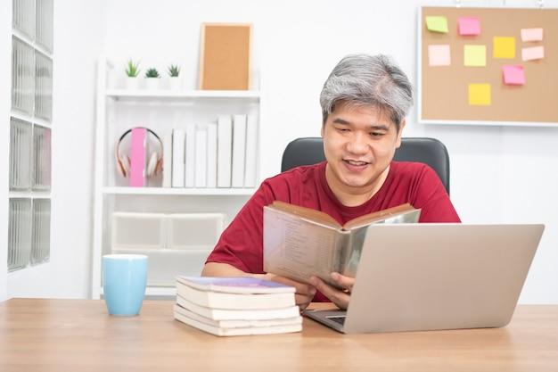 Расслабьтесь пожилой азиатский мужчина, читая книгу и слушая музыку в домашнем офисе.
