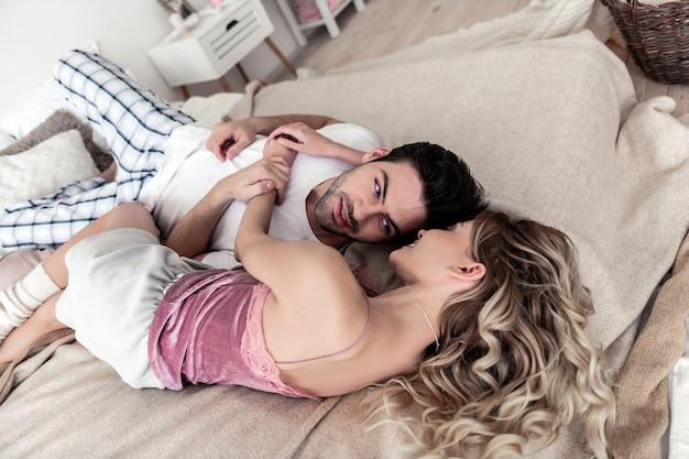 편하게 하다. 흰색 셔츠와 그의 긴 머리 아내 편안한 입고 잘 생긴 검은 머리 젊은 남자