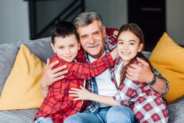 안심하다. 행복하고 쾌활한 할아버지는 웃고 손자와 함께 소파에 앉아 그들을 껴안고 있습니다.