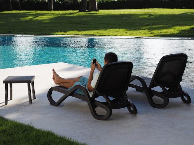 Отдохните в отеле с телефоном в руке. человек лежал на шезлонге у бассейна и с помощью смартфона. образ жизни.