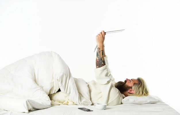 휴식 라이프 스타일 개념. 밤에 컴퓨터에서 작업 하는 침대에서 남자입니다. 프로젝트 관리자는 침대에서 작업을 완료합니다. 침대에서 노트북과 전화 작업을 하는 남자. pc를 사용하여 방에서 시간을 보내는 남성. 그림자 인터넷.
