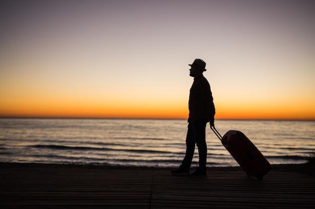 日没のシルエットでビーチでスーツケースと男をリラックスします。休日の旅行の概念。海の風景の背景にスーツケースを持つ男。