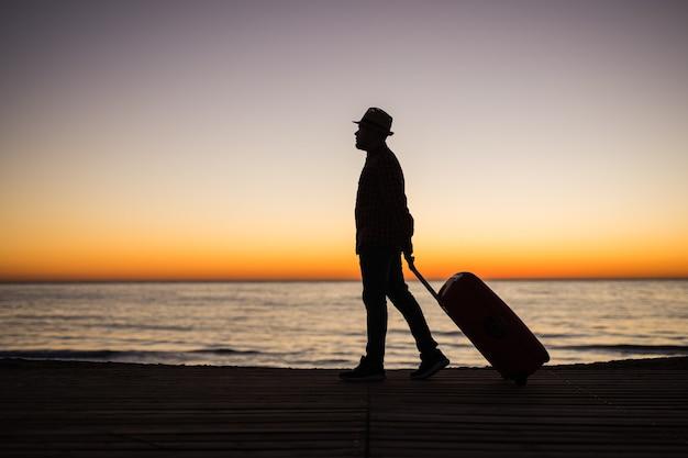 日没のシルエットでビーチでスーツケースと男をリラックスします。休日の旅行の概念。海の風景にスーツケースを持った男。